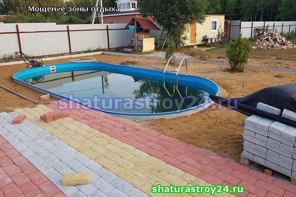 Подготовка основы для укладки и сама укладка тротуарной плитки английский булыжник около бассейна.